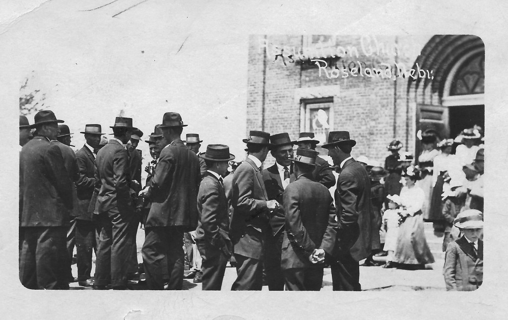The congregation always stood outside the church after Mass to visit.  Notice how the men and boys are all dressed in suits with hats.  This photo was taken about 1918 when people took pride in their appearance.
