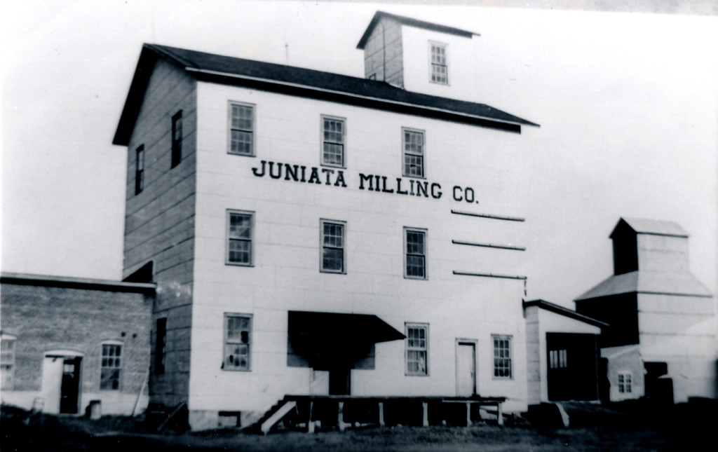 The brick building attached to the left side of the mill was the light plant.  Notice the Farmers Co-op Elevator to the right.